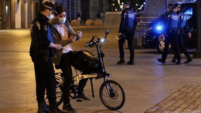 Un policía municipal de Madrid pide el justificante a un joven este miércoles después del toque de queda.