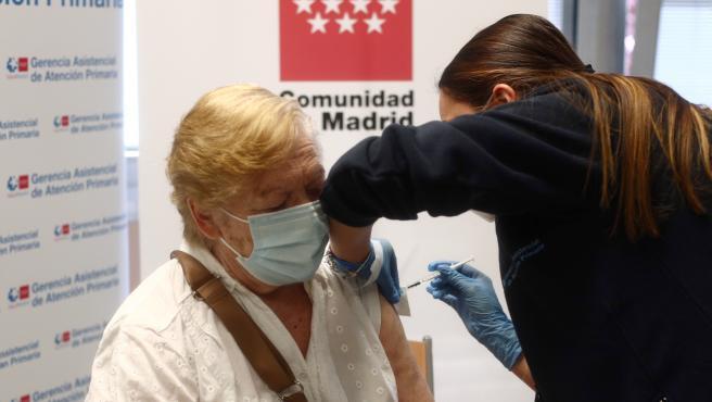 Una sanitaria inyecta la primera dosis de la vacuna de Pfizer contra el coronavirus a una anciana en el Centro de salud Rejas, a 6 de abril de 2021, en Madrid (España).