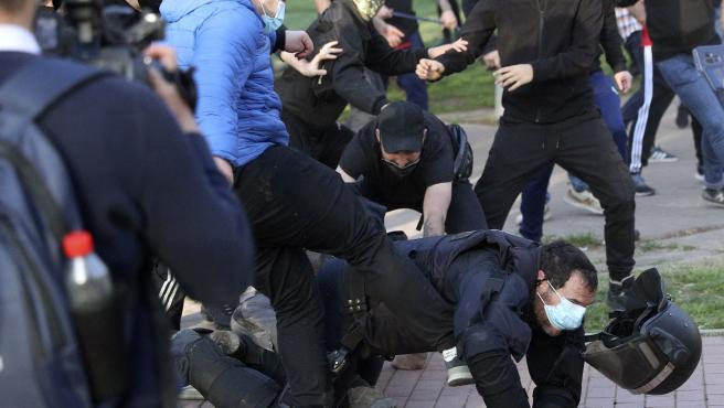 Unos manifestantes golpean a un policía en el acto de Vox en Vallecas.