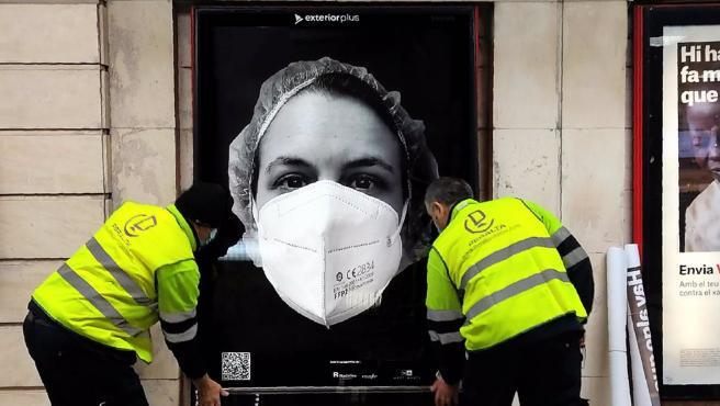 Dos operarios pegan un cartel de la campaña de apoyo a los sanitarios 'Behind de Mask', en una fotografía del 6 de abril del 2021. POLITICA BEHIND THE MASK