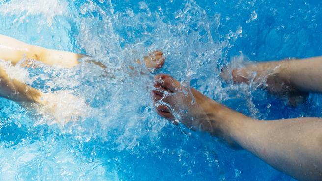 Dos personas chapotean con los pies en una piscina, en una imagen de archivo.