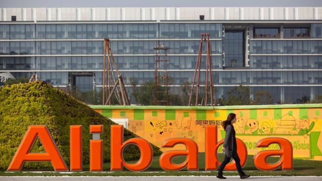 Un empleado pasa por delante del logo de Alibaba en su sede central en Hangzhou (China).
