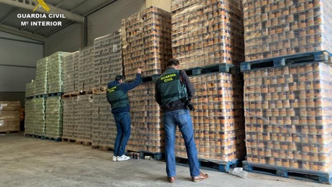 Dos agentes de la Guardia Civil revisan parte de los alimentos incautados.
