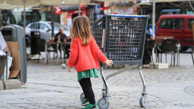Una niña camina junto a la terraza de un bar en el centro de Madrid.