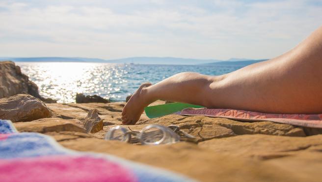 Una mujer toma el sol en la playa, en una imagen de archivo.