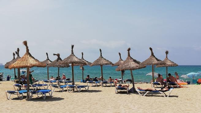 Archivo - Turistas en hamacas bajo las sombrillas de la Playa de Palma. Archivo.