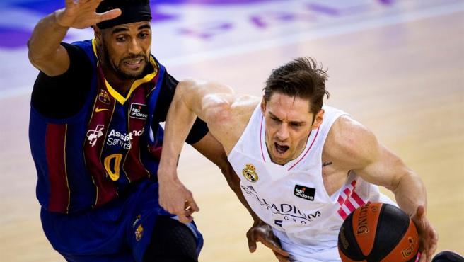 Un momento del partido entre Real Madrid y Barça. Causeur y Davies.