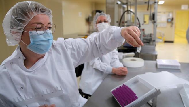Trabajadores de una planta francesa embotellan dosis de la vacuna de Pfizer contra el coronavirus.