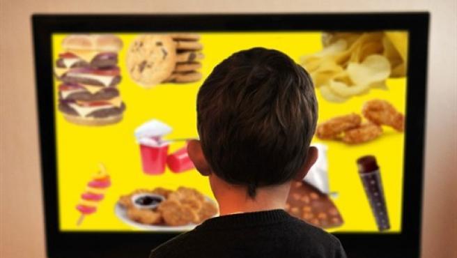 Imagen de archivo de un niño contemplando un menú de productos no saludables.