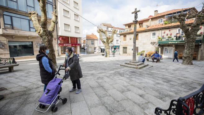 Dos mujeres conversan en una plaza de O Grove, el día en que entra en vigor el cierre perimetral del municipio, a 8 de abril de 2021, en O Grove, Pontevedra, Galicia, (España).