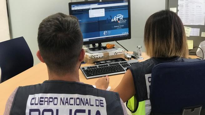 Archivo - Agentes de la Policía Nacional delante de un ordenador