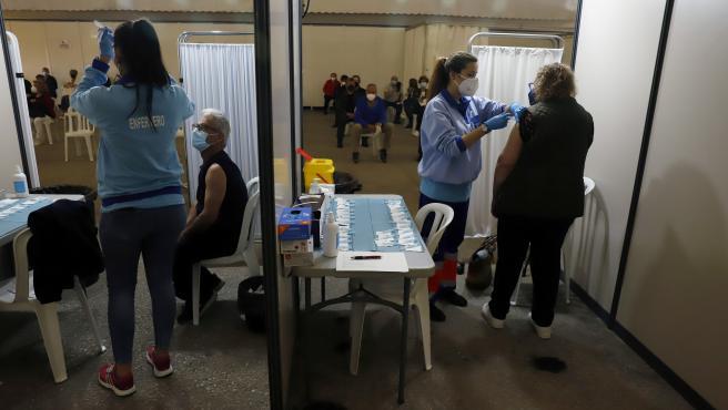 MLG (Vélez Málaga) 08-04-2021.-Varias personas hacen colas y reciben la vacuna contra el Covid_19, donde han empezado de nuevo la vacunación de AstraZeneca en el recinto ferial de Vélez Málaga.-ÁLEX ZEA.