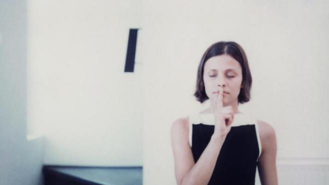 Una mujer pone en dedo índice en su boca en la señal internacional de silencio.