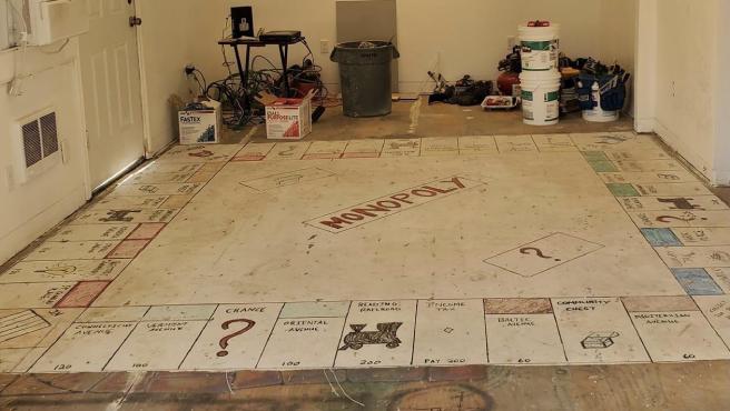 Una pareja encuentra un Monopoly gigante bajo la alfombra.