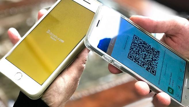 Two users with bitcoin wallets on their mobiles.