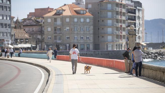 Varias personas pasean por el Paseo Marítimo de Sanxenxo, a 27 de marzo de 2021.