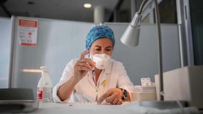 Archivo - Una enfermera prepara la vacuna Pfizer-BioNtech contra el COVID-19 antes de administrársela a un profesional sanitario en el Hospital de la Santa Creu i Sant Pau de Barcelona.