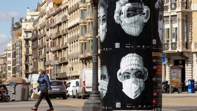 Una mujer camina junto a un cartel en Barcelona que reivindica la labor de los sanitarios con la iniciativa 'Behind The Mask'.