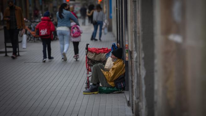 Archivo - Una persona sin techo permanece en el suelo de una calle cercana al Hospital de campaña instalado en la parroquia de Santa Anna, en Barcelona, Catalunya, (España), a 14 de noviembre de 2020.