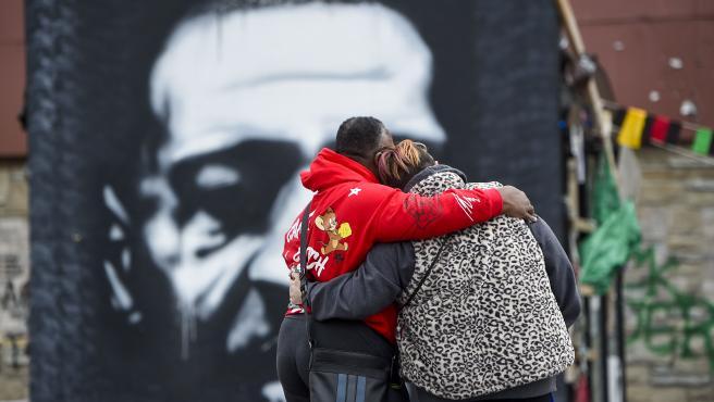 Una pareja frente a un retrato callejero de George Floyd