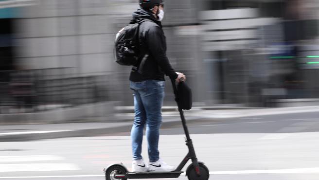 Archivo - Un hombre protegido con mascarilla monta un patinete eléctrico.