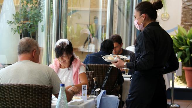 Una camarera sirve a dos clientes en un restaurante de Sant Carles de la Ràpita (Tarragona).