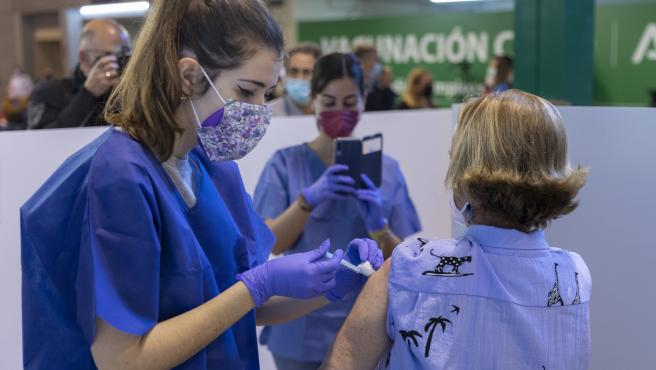 Una sanitaria vacuna a una mujer en la primera jornada de vacunación en el estadio, que quiso que otra trabajadora inmortalizara el momento. También lo hacían medios de comunicación que acudieron al estreno del 'vacunódromo'.