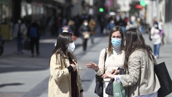 Un grupo de personas, con máscaras en el centro de Madrid.