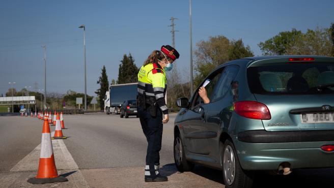 Una agente de los Mossos d'Esquadra pide un justificante a un conductor en un control en La Roca del Vallès (Barcelona).