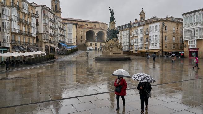 Dos personas se refugian con un paraguas de la lluvia en Vitoria.
