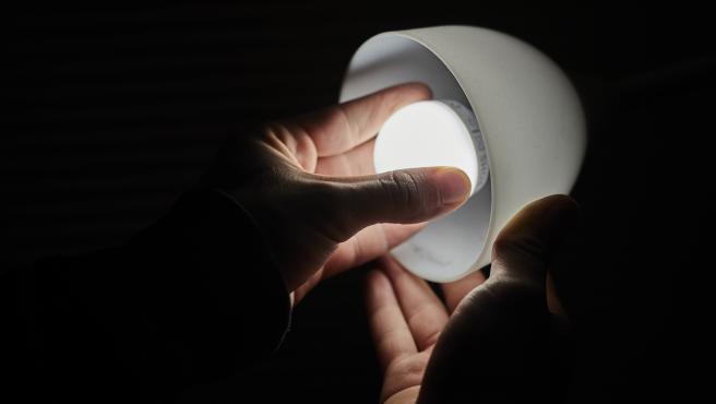 Archivo - Un hombre cambia la bombilla de una lámpara en una imagen de archivo.
