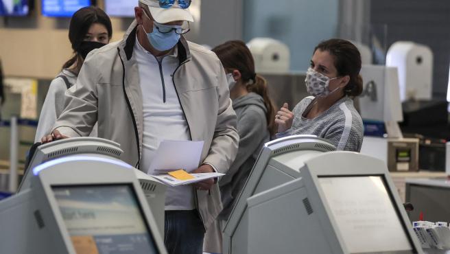 Viajeros con mascarillas por el coronavirus, en el Aeropuerto Internacional O'Hare de Chicago (EE UU).