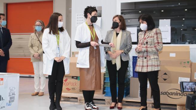 La consejera de Salud de La Rioja, Sara Alba (2i), y la ministra de Sanidad, Carolina Darias (d), conversan durante la recepción de un nuevo envío de vacunas de Pfizer/BioNTech contra el Covid-19
