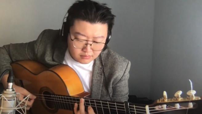 Can Wang tocando la guitarra.