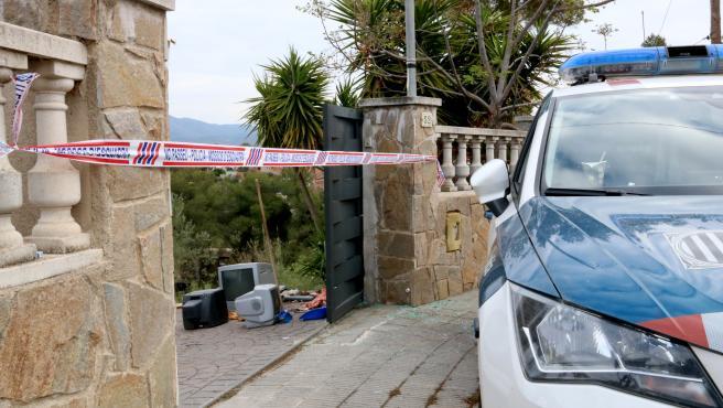Entrada a la casa de La Bisbal del Penedès (Tarragona) donde una mujer sufrió quemaduras mortales, presuntamente provocadas por su marido.  Se ven cintas policiales y dispositivos eléctricos en el suelo.