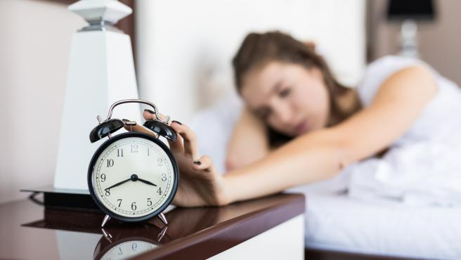 Imagen de archivo de una mujer apagando el despertador.