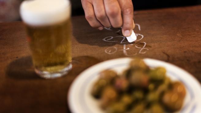 Un clásico, cañas, olivas y la cuenta con tiza sobre la barra.