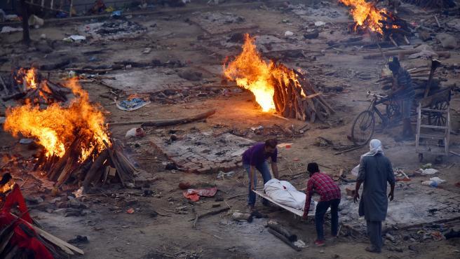 Varias personas transportan el cuerpo sin vida de una víctima del coronavirus a un campo de cremación improvisado en Nueva Delhi.