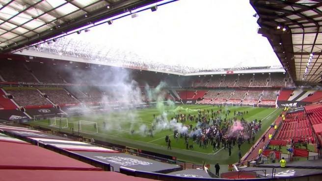 Aficionados del Manchester United invaden el césped de Old Trafford.