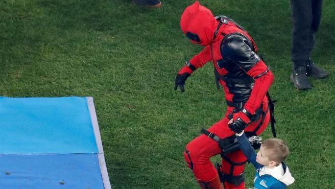 Artem Dzyuba picks up the league champion trophy dressed as Deadpool.