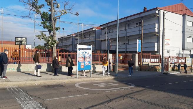 Varios personas esperan, manteniendo la distancia de seguridad por el covid, a que abran las puertas del Colegio Francisco de Quevedo, en Leganés, para depositar su voto de las elecciones del 4-M