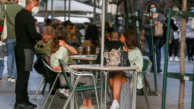Varias personas en la terraza de un bar en Madrid.
