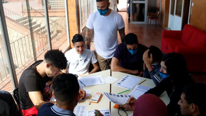 Diversos jóvenes del proyecto Llar d'Oportunitats participan en un taller en el equipamiento acompañados de educadores.
