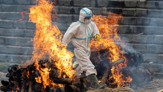 Un hombre con traje de protección incinera a fallecidos de covid en Nepal.