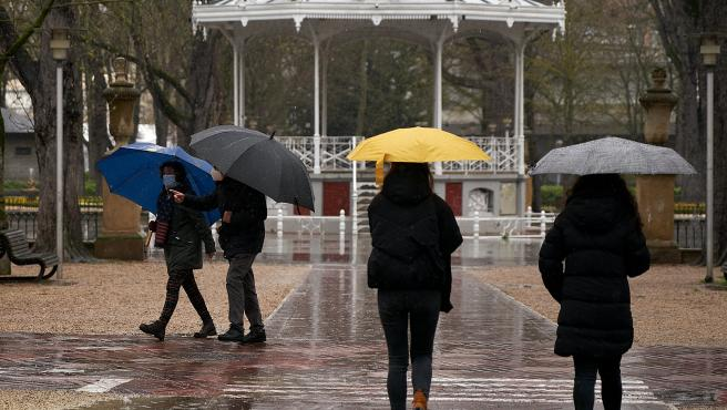 Varias personas se refugian con un paraguas de la lluvia.