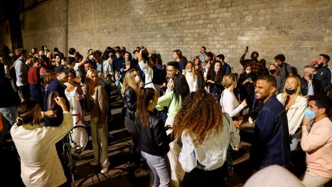 Jóvenes bailando en el Fossar de les Moreres en el barrio del Born en Barcelona donde cientos de personas se han concentrado tras el fin del estado de alarma y del toque de queda.