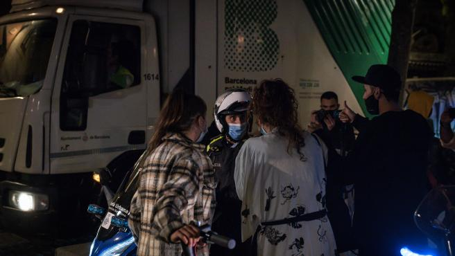 Un agente de la Guardia Urbana de Barcelona habla con dos jóvenes durante la madrugada de este domingo en el fin del estado de alarma.