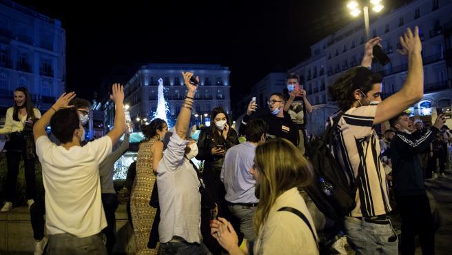 Varios jóvenes saltan y bailan en la Puerta del Sol de Madrid durante la noche en la que ha finalizado el estado de alarma y el toque de queda.