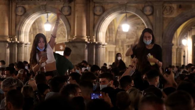 Dos jóvenes disfrutan de la noche encima de amigos suyos en una Plaza Mayor en Salamanca repleta de personas tras el fin del estado de alarma.