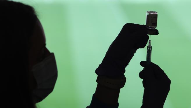 Un profesional sanitaria sostiene una jeringuilla.
